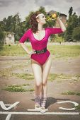 Beautiful brunette woman in pink retro body outfit with ponytail hairstyle and soda bottle in her ha