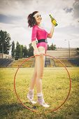 Beautiful brunette woman in pink retro body outfit with ponytail hairstyle hula hoop and soda bottle