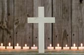 Wooden cross by row of burning candles with rustic wood background