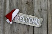 Welcome sign with Christmas Santa Claus hat hanging on old wooden background