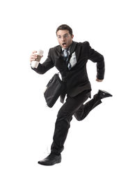 stock photo of running-late  - young attractive businessman with take away coffee running late to work wearing suit and tie hurry up to office in stress and overwork concept isolated on white background - JPG