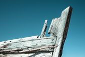 Постер, плакат: Old wooden boat bow against blue sky