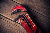 stock photo of pipe wrench  - vintage pipe wrench on a wooden background - JPG
