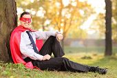 pic of early-man  - Joyful man in superhero outfit sitting on a grass - JPG