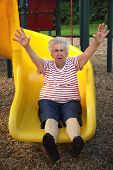 stock photo of unnatural  - Senior citizen woman with arms upraised on a playground sliding board - JPG