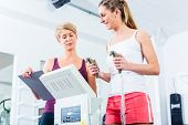 stock photo of body fat  - Trainer with body fat scale in gym measuring woman - JPG