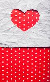 picture of cut torn paper  - White torn paper in heart shape symbol over red background - JPG