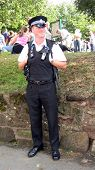 foto of truncheon  - British policeman/sergeant  wearing uniform standing smiling.People at work