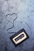 stock photo of magnetic tape  - audio cassette with magnetic tape in shape of heart on grunge background - JPG