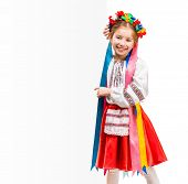 stock photo of national costume  - cute little girl in the Ukrainian national costume stand behind white board with space for text - JPG