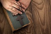 picture of fingers crossed  - closeup of hands holding vintage cross on Bible - JPG