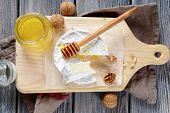 stock photo of brie cheese  - Brie cheese with honey and walnuts on a cutting board - JPG