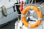 image of nautical equipment  - Modern yacht safety equipment orange lifebuoy mounted on railings - JPG
