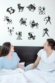 picture of horoscope signs  - Man and surprised woman in bedroom surrounded looking up at horoscope zodiac 12 signs - JPG