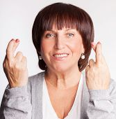 pic of fingers crossed  - Mature woman with crossed fingers - JPG