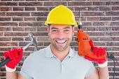 image of hammer drill  - Happy repairman holding hammer and drill machine against red brick wall - JPG