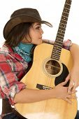 stock photo of cowgirls  - a cowgirl hugging her guitar close to her body - JPG