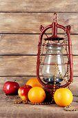 picture of kerosene lamp  - Kerosene lamp with beads and fruits on wooden planks background - JPG