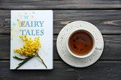 pic of mimosa  - Fairy Tales book with cup of tea and sprig of mimosa on wooden background - JPG