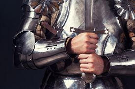 stock photo of sword  - knight wearing armor and holding two - JPG