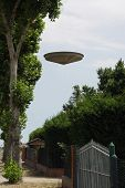 picture of ovni  - a flying saucer hovers above the italian countryside - JPG