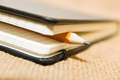 stock photo of memento  - notebook with a blank sheet and pencil on the old tissue - JPG