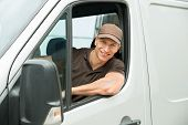 stock photo of moving van  - Young Happy Delivery Man Driving Service Delivery Van - JPG