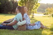 stock photo of she-male  - Cheerful loving couple is sitting on green grass and relaxing - JPG