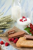 foto of white-milk  - Vertical photo of several cereal biscuits on jute cloth with raspberries around - JPG
