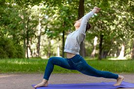 stock photo of virabhadrasana  - Serene beautiful sporty young woman working out on blue mat on the street in park alley doing high lunge exercise virabhadrasana 1 warrior 1 posture surya namaskar complex full length - JPG