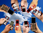 Many hands holding mobile phones