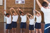 Teacher teaching exercise to school kids in basketball court at school gym poster
