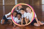 Portrait of school kids looking through hula hoop in basketball court at school gym poster