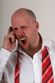 stock photo of angry man  - An angry man yelling on a mobile phone in shirt and loose tie - JPG
