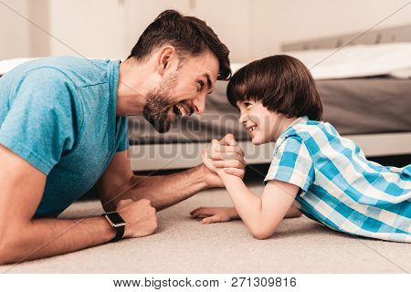 poster of Father And Son Lying On Floor And Have Fun At Home. Sitting Boy. Young Father. Young Bearded Man At