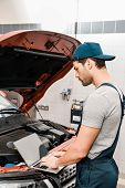 Side View Of Auto Mechanic Working On Laptop At Automobile With Opened Car Cowl At Mechanic Shop poster