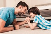 Father And Son Lying On Floor And Have Fun At Home. Sitting Boy. Young Father. Young Bearded Man At  poster