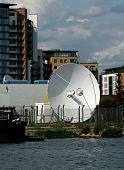 Постер, плакат: Спутниковая антенна базу вблизи жилых квартир и воды
