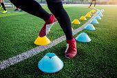 Soccer Player Jogging And Jump Between Cone Markers On Green Artificial Turf For Soccer Training. poster
