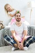 Cute Little Daughter In Pink Tutu Skirt Doing Hairstyle To Happy Father With Red Lipstick poster
