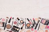 Makeup cosmetics such as eyeshadows, lipstick, mascara and makeup accessories on white, wooden backg poster