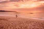 Surf Woman With Surfboard Go To Ocean For Surfing. Surfer Woman On Beach At Bright Sunset poster