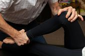 Hands Of A Chiropractor Adjusting The Leg Of A Young Girl.  His Hands Are At Her Knee And Ankle As H poster