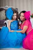 ?ute little girl, a child with mother in a gorgeous dress in the room