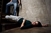 Battered woman lies lifelessly at the bottom of stairs with a faceless man holding a belt, a concept