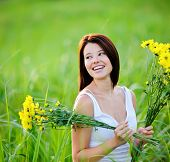 picture of beauty nature  - Adorable girl with flowers poses in a field during summer afternoon - JPG