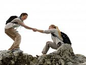 stock photo of climb up  - Hiker woman helps her friend climb up the last section of mountain - JPG
