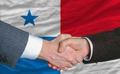 Businessmen Handshake After Good Deal In Front Of Panama Flag