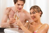 Couple is doing wellness with champagne; presumably it is their honeymoon