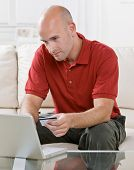 Man making online shopping purchase on laptop with credit card